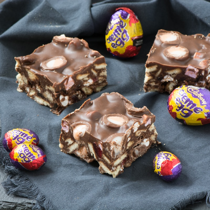 Three pieces of Creme Egg rocky road surrounded by Creme Eggs in their wrappers.
