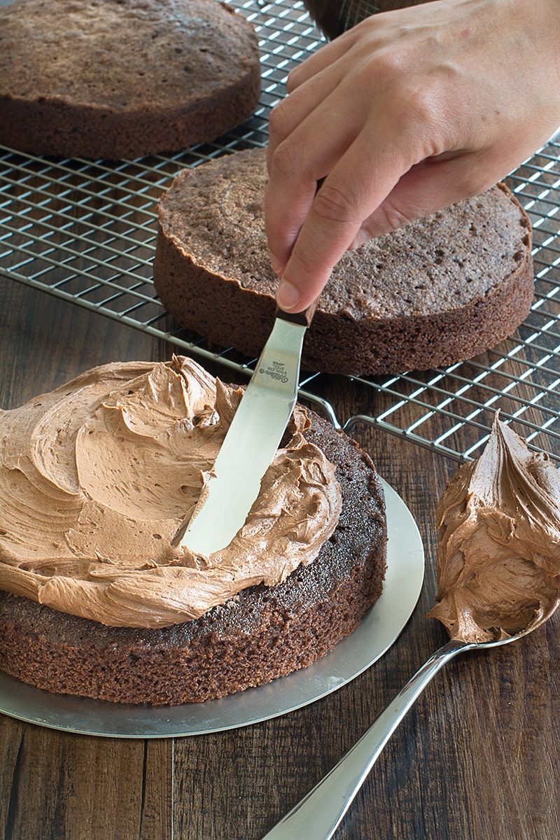 Spreading chocolate buttercream onto a round chocolate birthday cake using a palette knife. There are two more layers of chocolate cake on a cooling rack in the background.