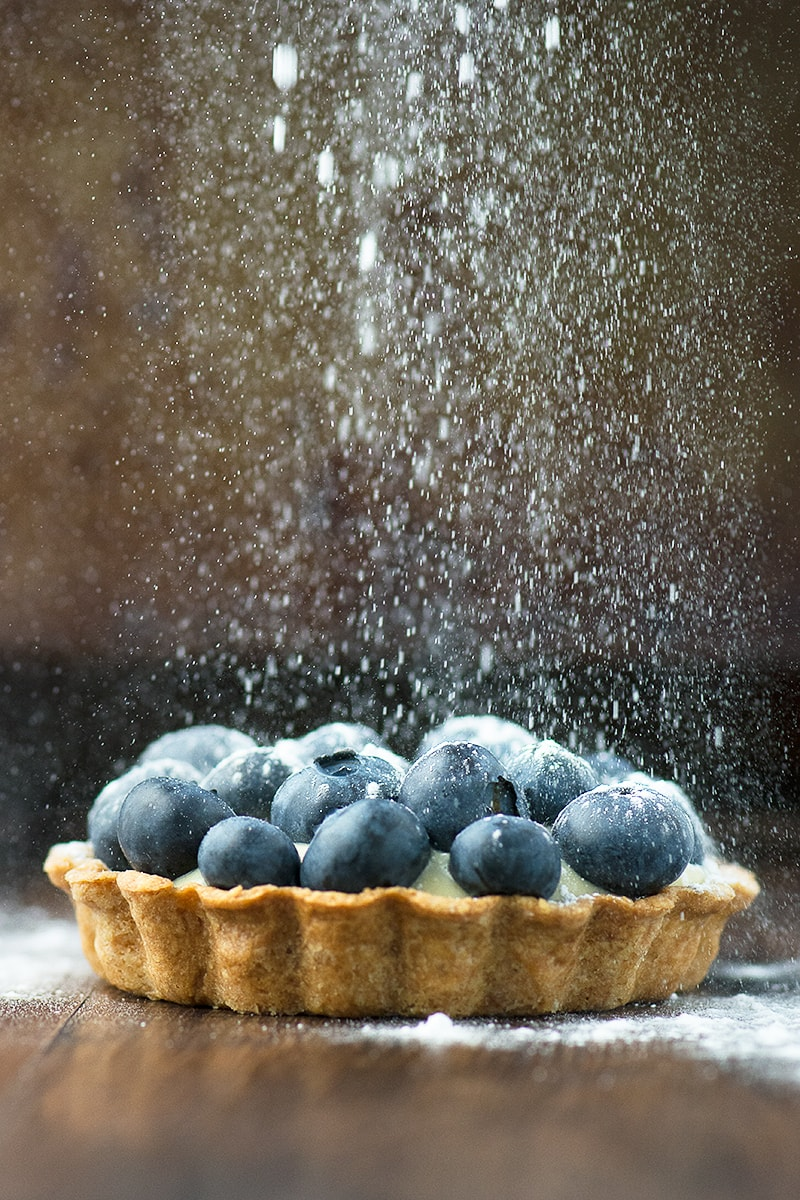 Summer berry and custard tarts - crispy pastry filled with creamy vanilla custard and topped with fresh blueberries with a sprinkling of icing sugar.
