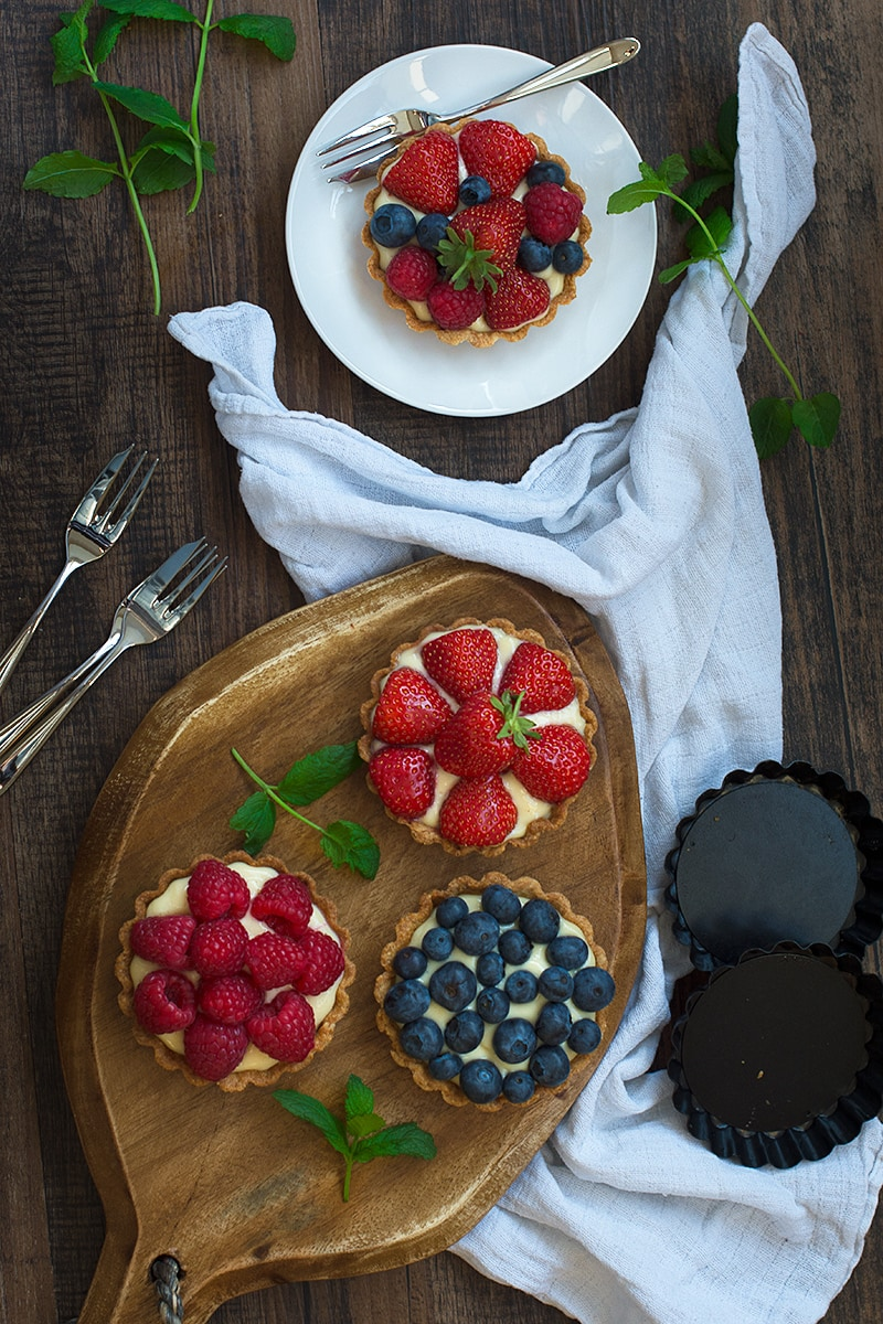 Summer berry and custard tarts - crispy pastry filled with creamy vanilla custard and topped with fresh, juicy berries. A delicious, elegant summer dessert.