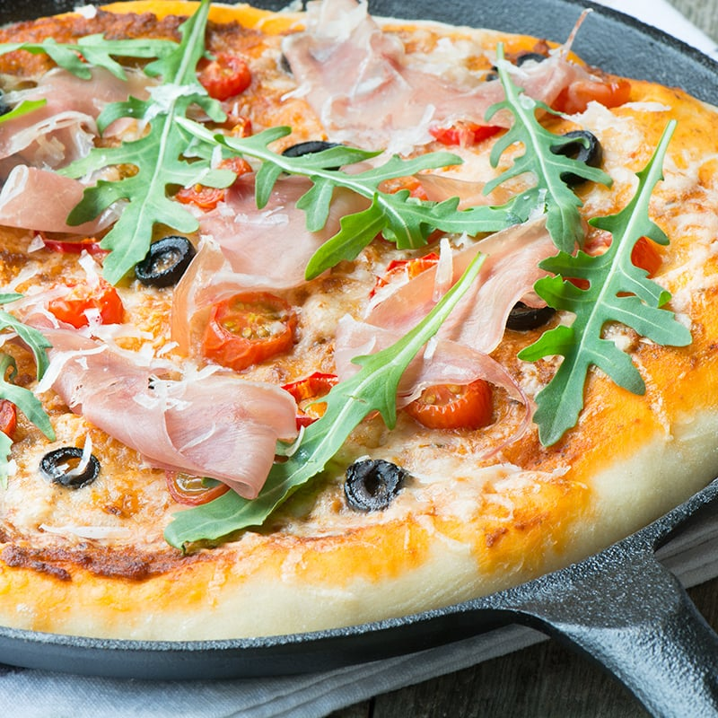 A delicious homemade pizza topped with sun dried tomato pesto, olives, chillies and Grana Padano cheese and then finished with Prosciutto di San Daniele and rocket.