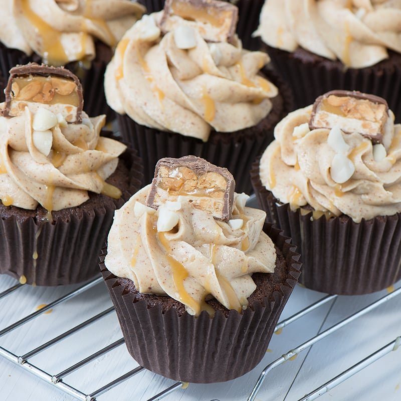 Snickers Cupcakes - Chocolate Cupcakes filled with caramel sauce and topped with smooth peanut buttercream, more caramel, crunchy peanuts and a little slice of Snickers.