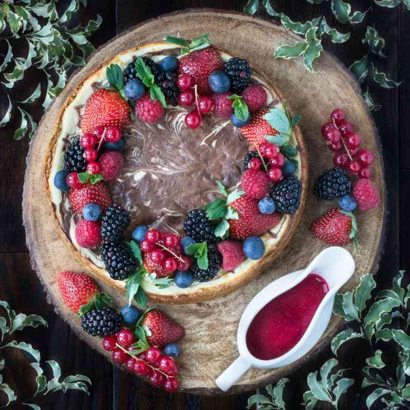 Looking down on a baked chocolate marble cheesecake  next to a jug of redcurrant coulis.