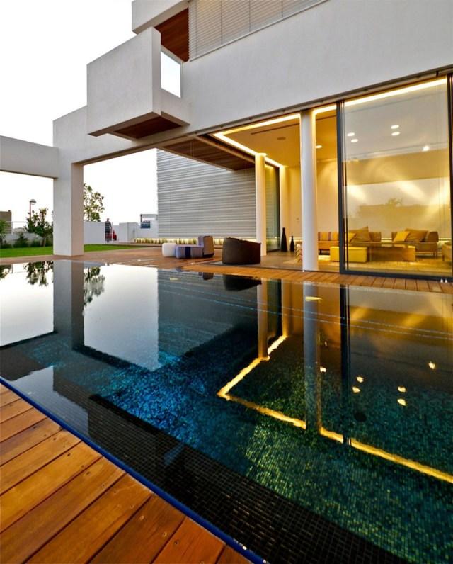 スイミングプールに映るミニマリストのモダンな邸宅