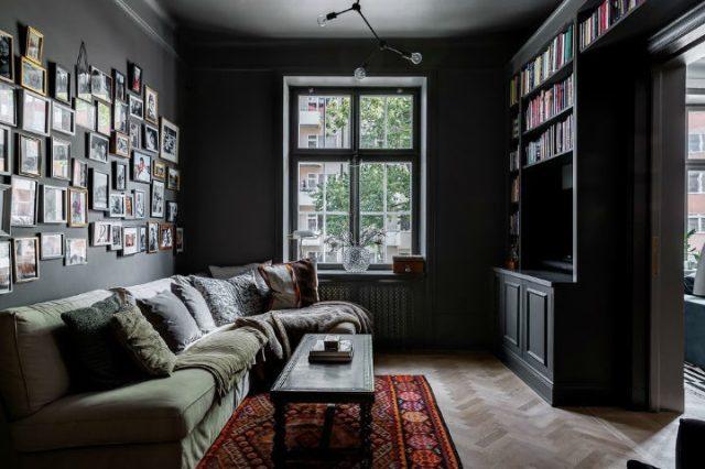 黒い壁と緑のソファのある小さなリビングルーム