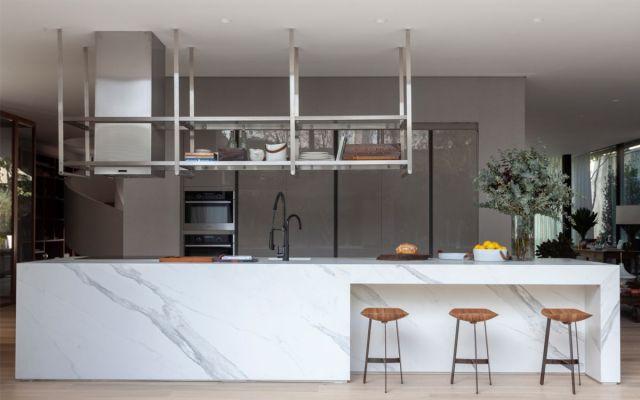 オープンプランのキッチンには、大きな白い大理石の島があり、仕切りとしても機能します