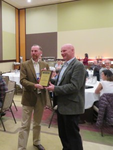 Photo of CHARM President David Clampin presenting the 2019 Hollander Award to Neil Ewins