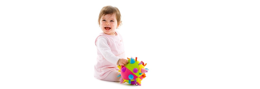 baby girl sitting on floor playing with toy smiling