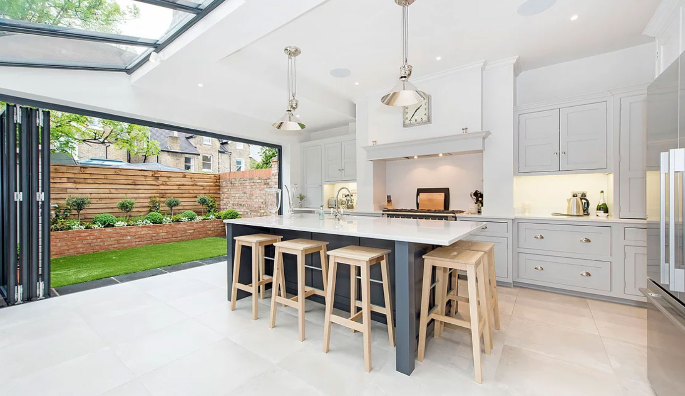 pale grey shaker style kitchen with island and bi fold doors