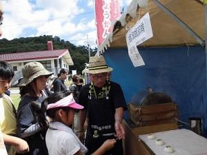 六呂師高原アルプス音楽祭2014 お嬢さんが持っている焼きごてを誘導している御菓子司おさやの旦那さん/どこまでもアマチュア