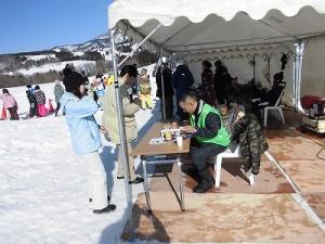 さかだに雪まつり スノーモービル体験の受付をしているお客さん/どこまでもアマチュア
