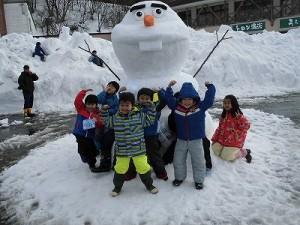 さかだに雪まつり 雪像づくりコンクール オラフの雪像前でポーズをとる子どもたち/どこまでもアマチュア