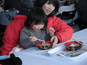 さかだに雪まつり ママの膝の上でおそばを食べるお嬢ちゃん/どこまでもアマチュア