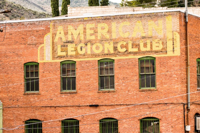 American Legion club sign just below the roof on multi-story building.