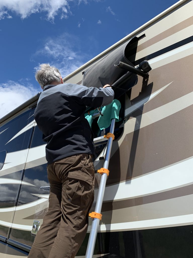 A man on a ladder that is leaning up against an RV.