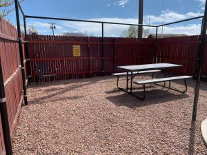 A picnic table on gravel, with a gazebo structure and a fence all around.