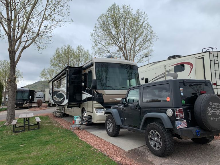 A side view/angle of the RV park space, showing an RV in the back and a black Jeep Wrangler in the front.