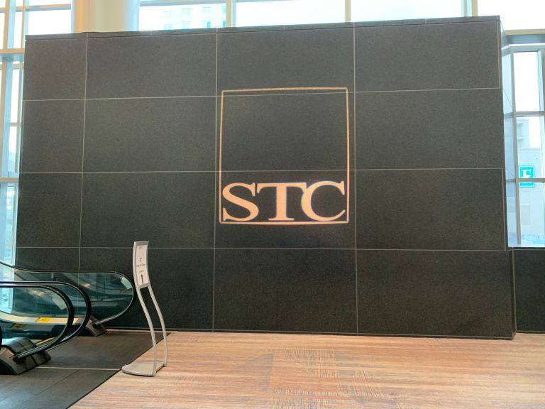 The STC logo at the top of the escalator on the 3rd floor of the hotel.