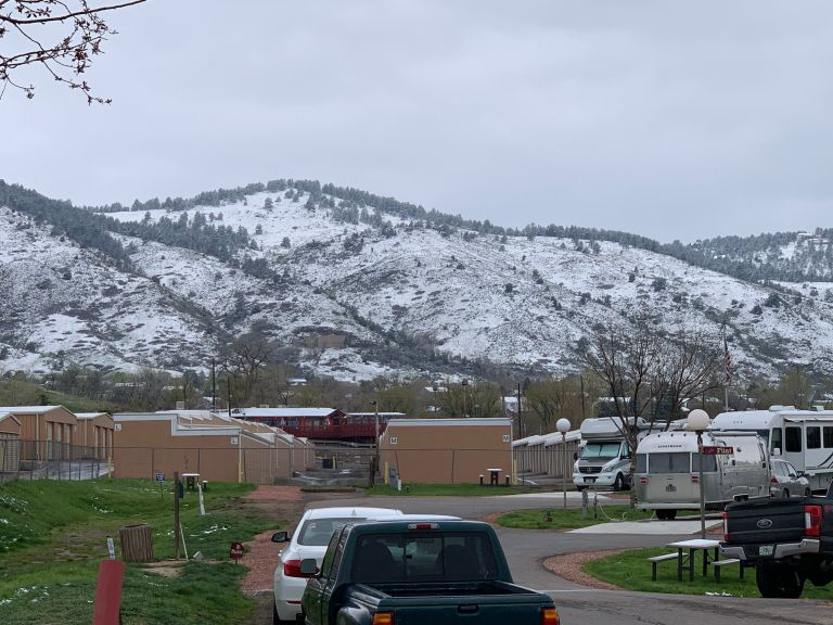Snow covered mountains in the background, with vehicles and buildings in the foreground.