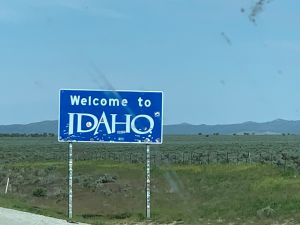 The Welcome to Idaho sign, with blue background and white letters.