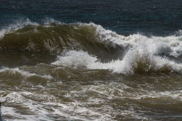 Waves cresting over into a curl while splashing down.
