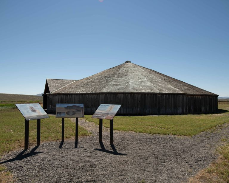View of the round barn with three signs in front.