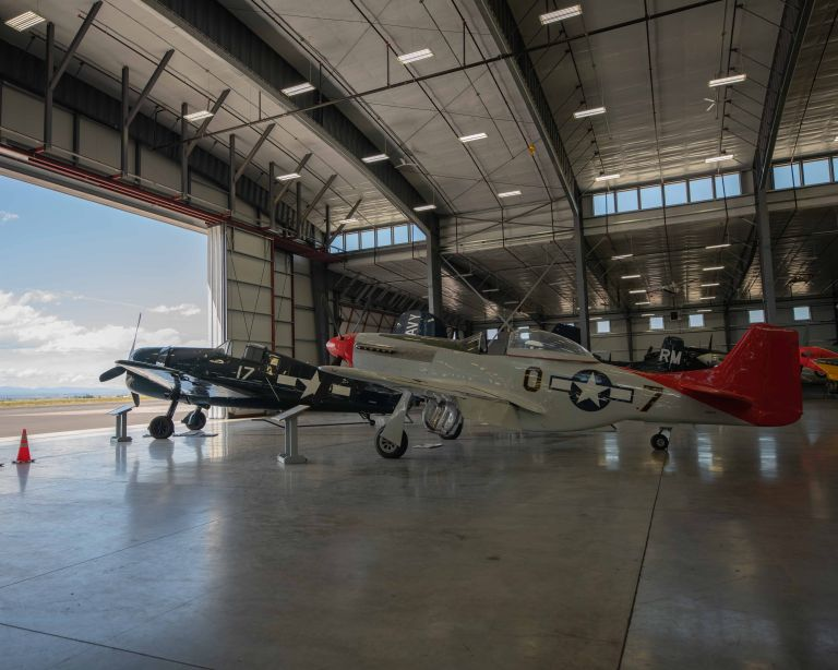 The P-6 Mustang and the Grumman F6F-5 Hellcat from the side, showing both planes with the hangar door open.