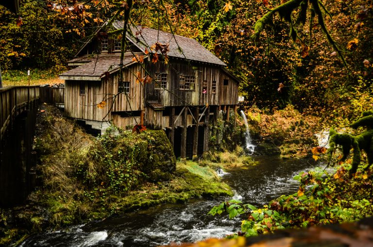 historic wooden building with creek and fall leaves