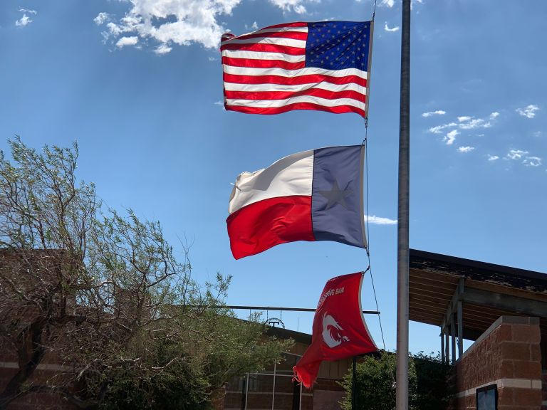 Three flags in the wind, with blue skies in the background. The US flag is on top, the Texas state flag is in the middle, and a red Burning Ban flag is on the bottom.