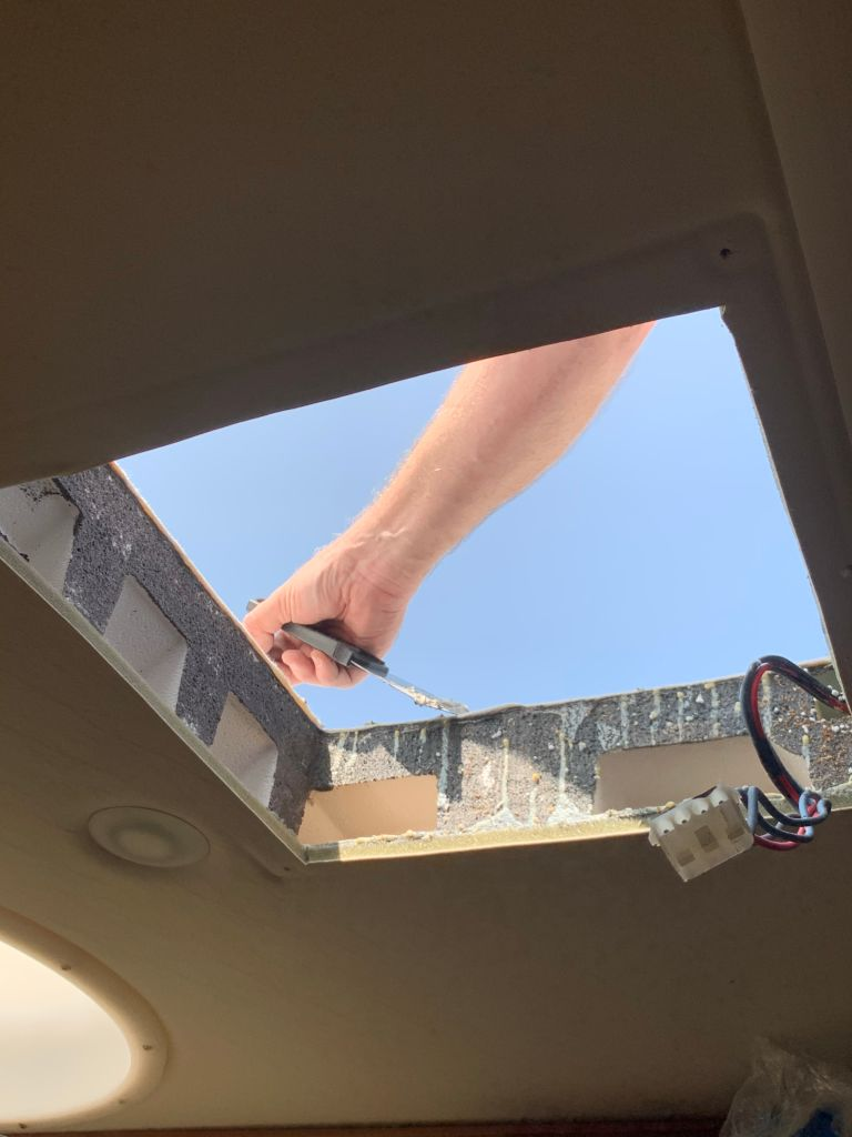 A hand scraping a roof through a hole in the ceiling.