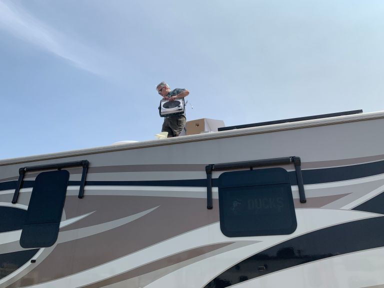 A man standing on the roof of an RV.