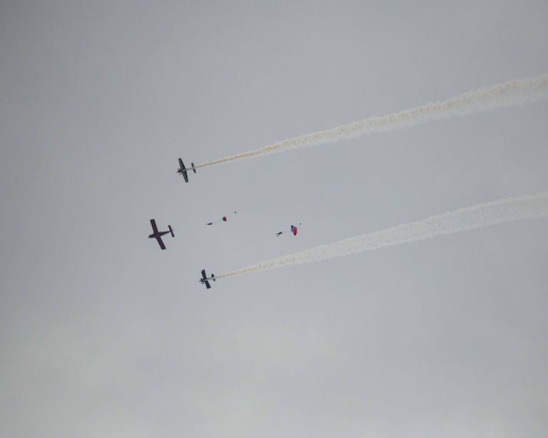 Three planes and two parachutists in the cloudy sky.