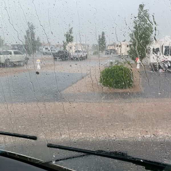 Rain coming down an RV windshield, with dirty water on the road in front of it.