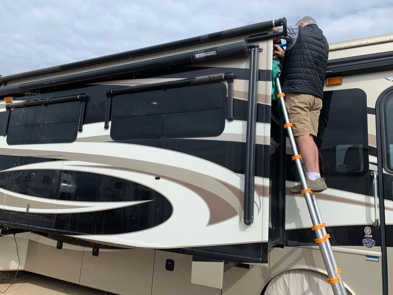 A man on a ladder, propped against the slideout of a Class A RV.