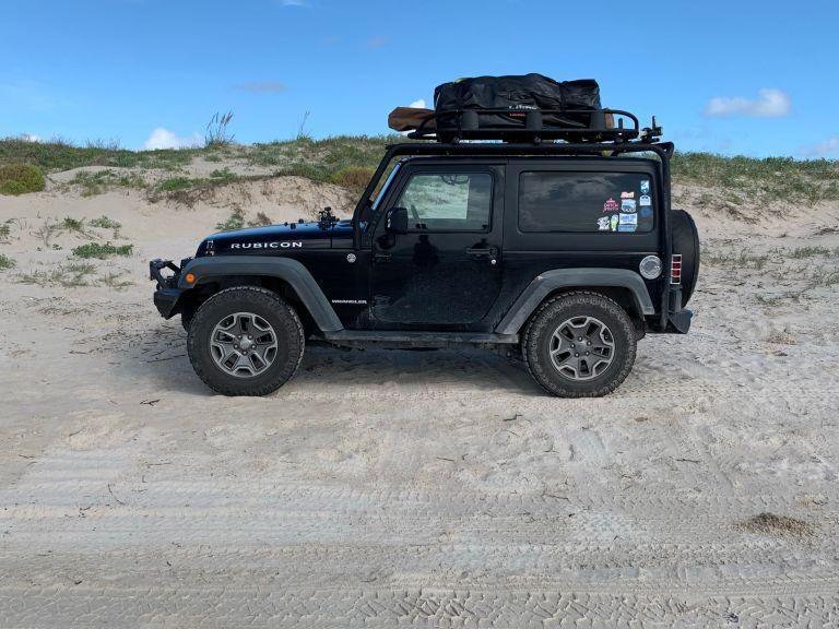 A black Jeep Wrangler on the beach.