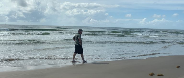 A barefoot man walking on the sand with waves lapping over his feet.
