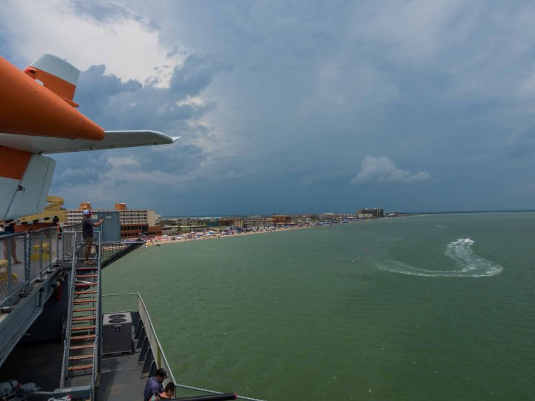 A view of the Gulf of Mexico with rain clouds above.