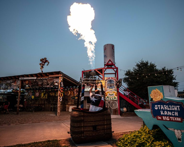 A taco food court, a hot air balloon with one burner pointing upwards, and a texas sized sign that says Starlight Ranch.