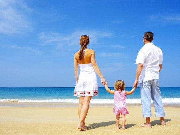 Семья у моря: мама, папа и маленькая дочка