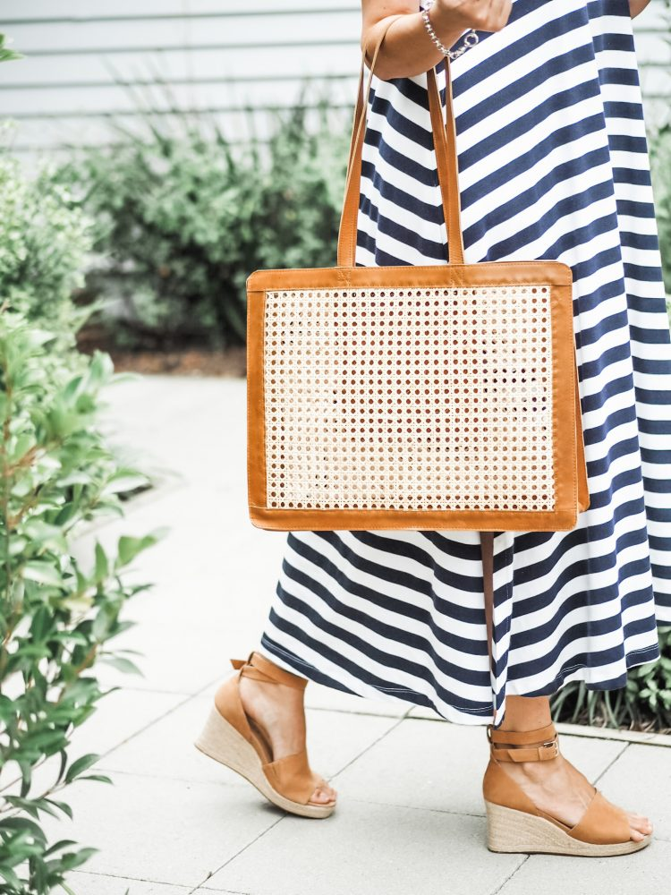 tan bag and shoes worn with a navy and white tripe dress