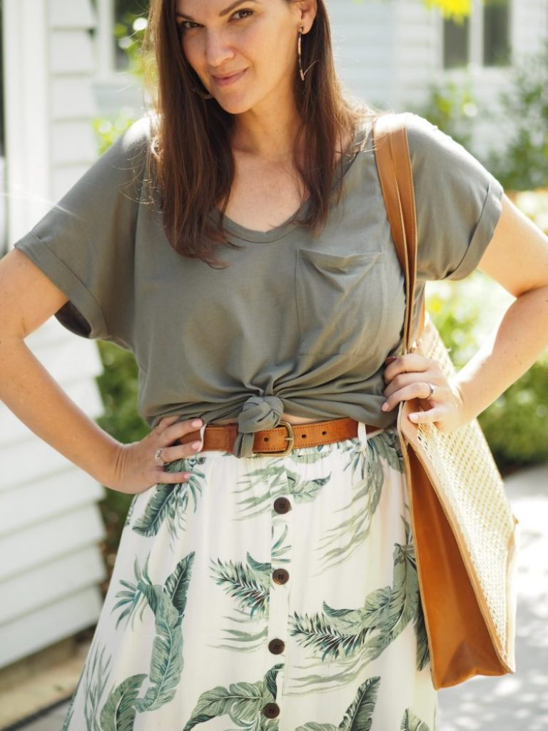 woman wearing green tee and printed skirt with tan belt and bag