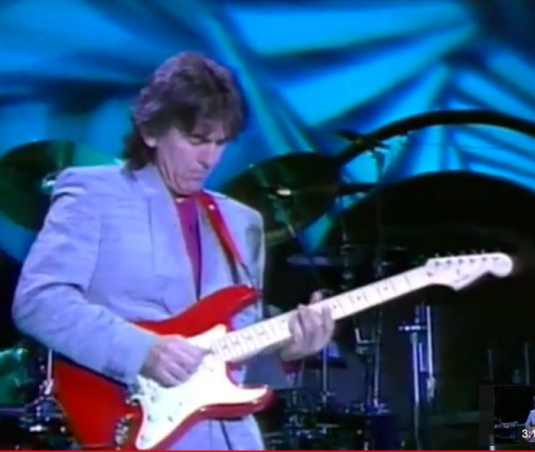 George Harrison playing a red Stratocaster