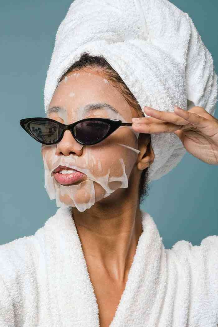 content young black woman wearing sunglasses during skin care treatment after bath