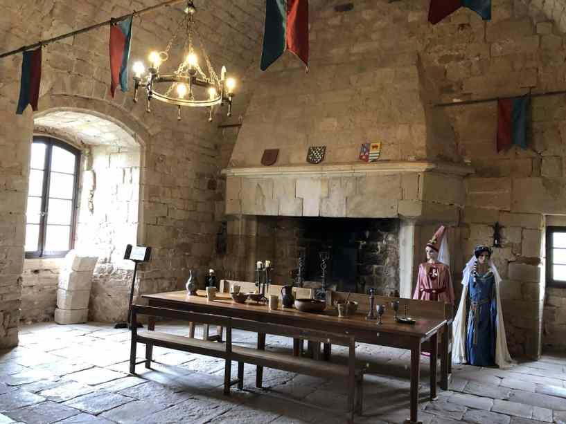 salle principale du chateau, grande cheminée et tables pour nombreux convives