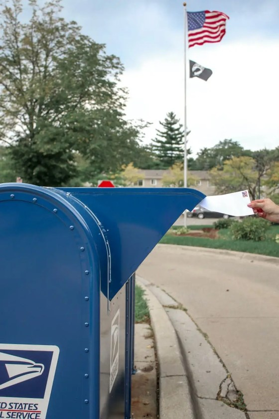 crop person putting envelope in mailbox on street