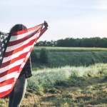 Girl with American USA flag in a field