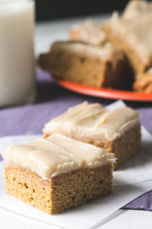 a photograph of two pumpkin blondies iced with brown sugar cream cheese icing with a plate of blondies and a glass of milk in the background