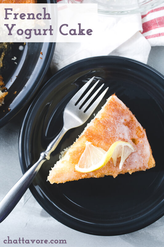 an overhead photograph of a slice of French yogurt cake with a lemon twist on top and a fork