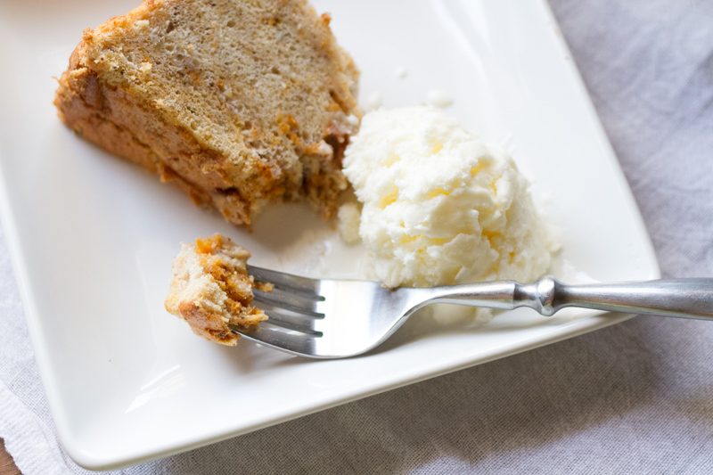 a photograph of a slice of pumpkin angel food cake from scratch on a plate with a scoop of ice cream and a fork with a bite of pumpkin angel food cake on it