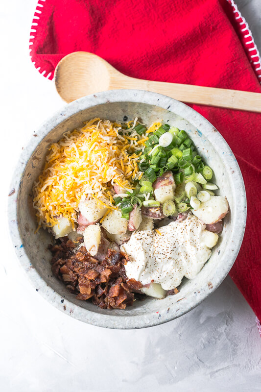 an overhead picture of a bowl of ingredients for loaded baked potato salad that have not been mixed